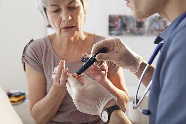 médico medindo glicemia em paciente idosa com diabetes tipo 2