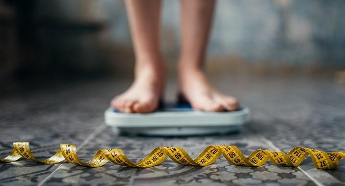 pés de menina com anorexia em cima de uma balança com um metro na frente