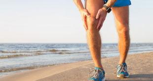 homem correndo na praia sente dor no joelho por lesão de menisco