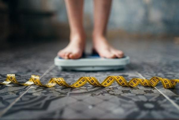 pés de menina em cima de balança com fita métrica na frente, possível obesidade