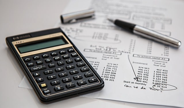 calculadora ao lado de folha com caneta de alguém planejando investimentos