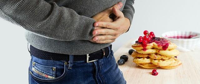 homem com dor de barriga depois de comer coisas com leite porque tem intolerância à lactose