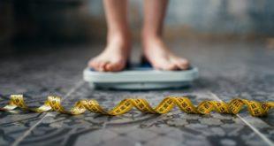 pés de pessoa com obesidade se pesando, com fita métrica na frente