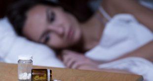 mulher com insônia acordada na cama, olhando para pílulas de dormir na mesinha de cabeceira