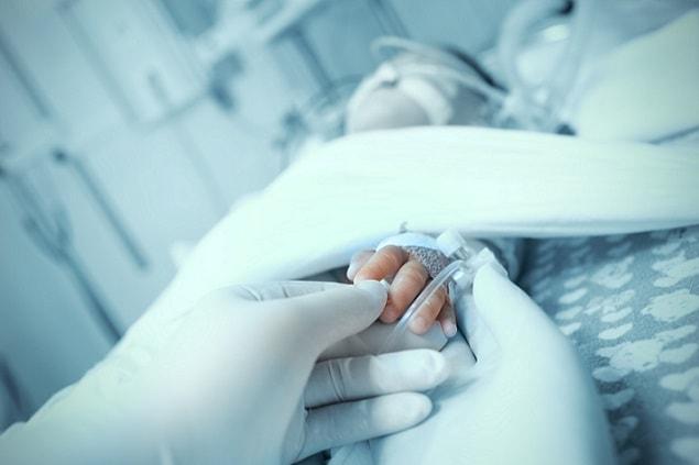 médico segurando mão de bebê em uti pediátrica para hipotermia terapêutica