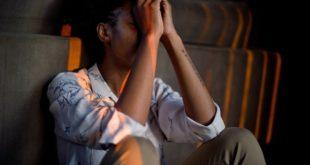 mulher com estresse sentada no chão com as mãos na cabeça