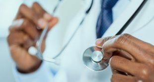 médico segurando estetoscópio, mãos em foco