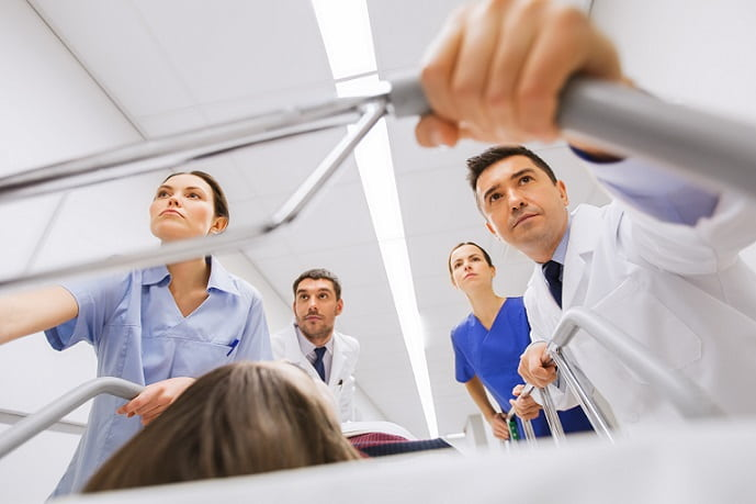 médicos levando paciente para unidade de emergência para realizar ACLS de acordo com protocolo do AHA 2019