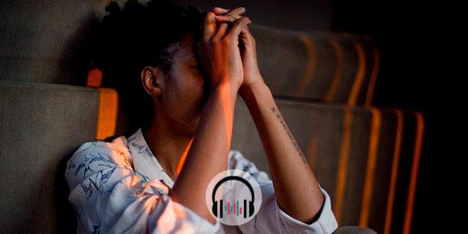 mulher negra com as mãos na cabeça preocupada com a saúde mental