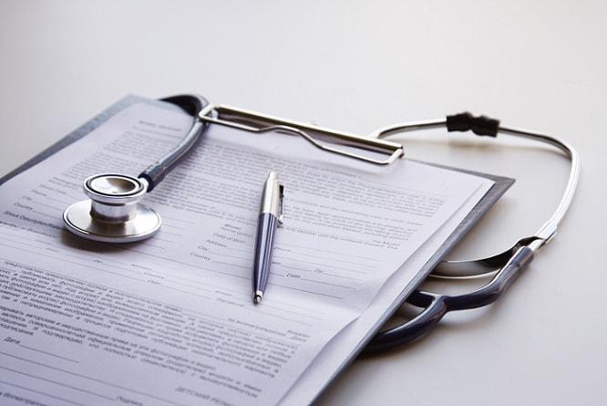 estetoscópio em cima da mesa com prontuário ao lado sobre saúde