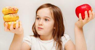 menina com risco de obesidade infantil olhando fixamente para os donuts, em uma mão, enquanto segura também uma maçã em outra