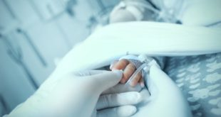 bebê com apneia da prematuridade em UTI pediátrica, mãos do médico segurando a mão do bebê em foco