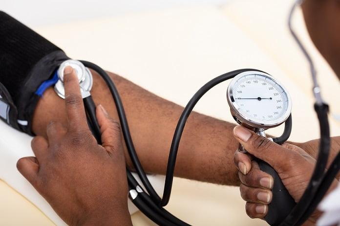 foco nas mãos do médico aferindo pressão arterial em paciente com hipertensão