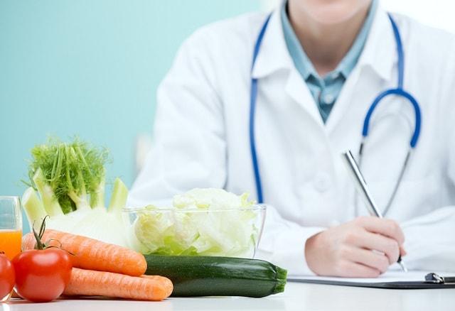 médico de nutrologia escrevendo em uma mesa com alguns alimentos ao lado