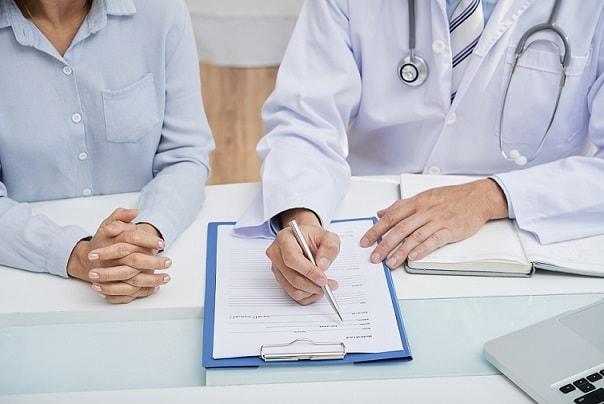 médico conversando com paciente sobre espiritualidade e mostrando no papel o que deve ser feito