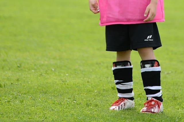 parte inferior de criança com roupa de futebol em um campo, combatendo o sedentarismo