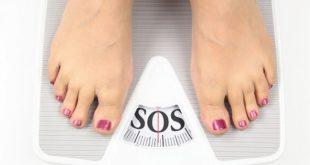 pés de mulher em balança escrito SOS, em referência à obesidade