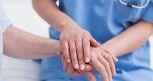 enfermeira cuidando de paciente com dispneia, foco nas mãos dadas