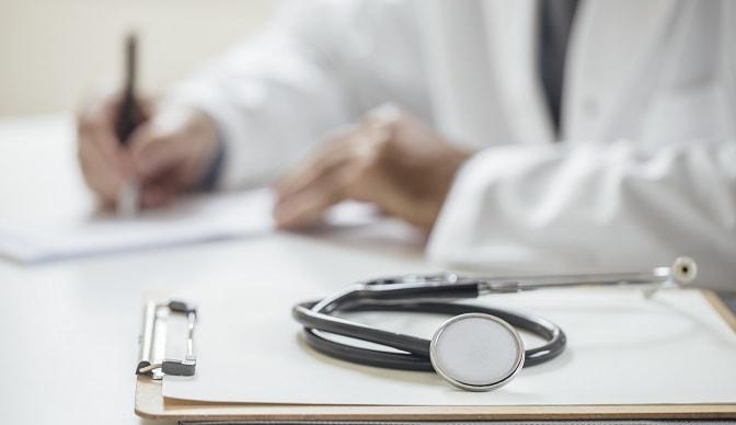 médico escrevendo relato de caso de herpes congênita, prontuário e estetoscópio em foco na frente das mãos do médico