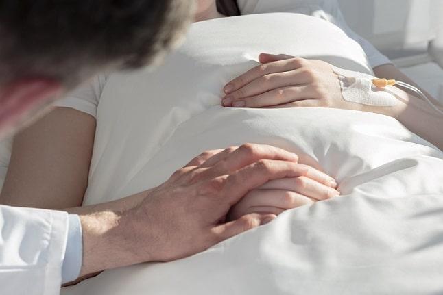 psicólogo segura mãos de paciente internada em hospital por doença crônica