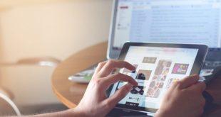 mãos de pessoa usando tablet, com computador ao fundo, devido ao vício em internet