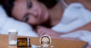 mulher deitada com insônia, foco na mesa de cabeceira com remédios