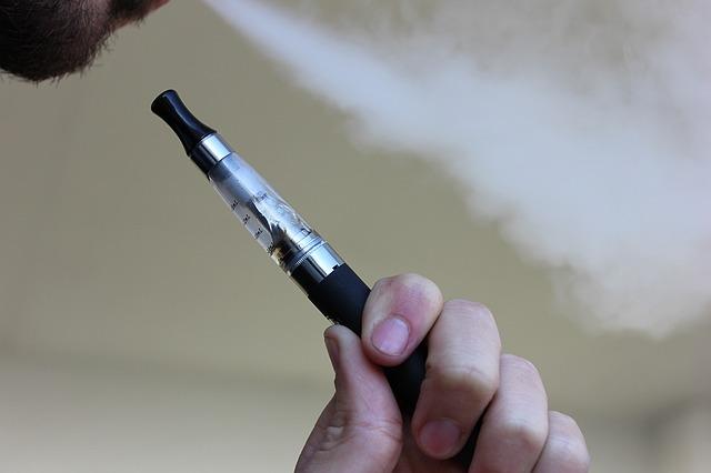 mão de fumante segurando um cigarro eletrônico enquanto solta a fumaça pela boca