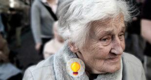 mulher idosa com demência, apresentando sinal do aplauso, olhando para o lado