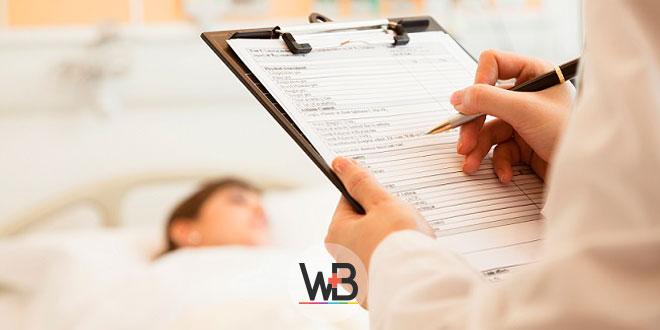 médico escrevendo em prontuário de paciente internada com câncer de mama