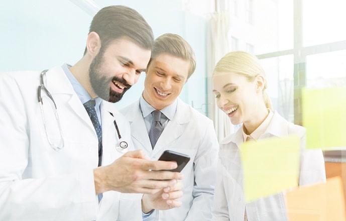 grupo de médicos lendo no celular notícias médicas