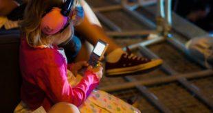 menina com fone de ouvido jogando gameboy, sem os pais se preocuparem com a saúde de crianças