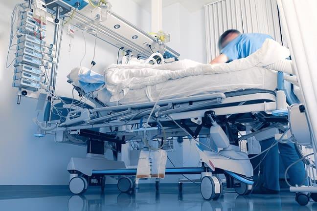enfermeiro ao lado de cama de terapia intensiva com paciente em ventilação prona