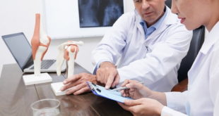 médico com enfermeira mostrando prótese articular