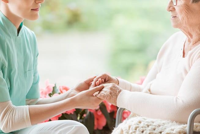 enfermeiro cuidador segurando as mãos de paciente idosa em cadeira de rodas
