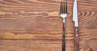 garfo e faca em cima de mesa vazia representando eliminação da gordura trans