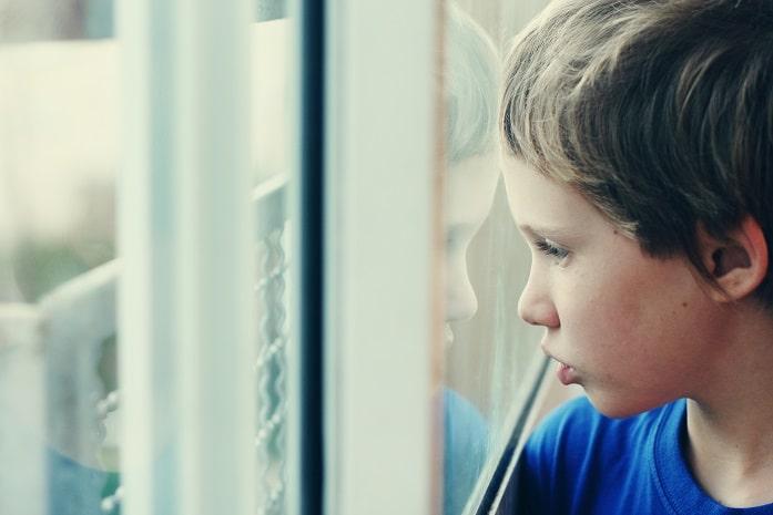 criança com autismo olhando pela janela