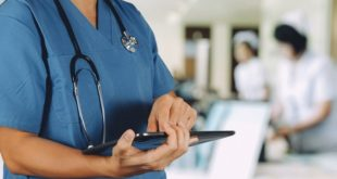 médico em centro de terapia intensiva, segurando tablet com notícias médicas