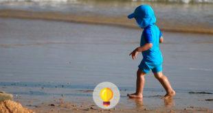 criança brincando na praia, exposta à insolação