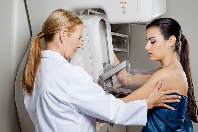 médica assistente realizando mamografia em mulher com suspeita de câncer de mama