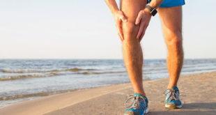 homem com as mãos no joelho após correr na praia, devido osteoartrite de joelho