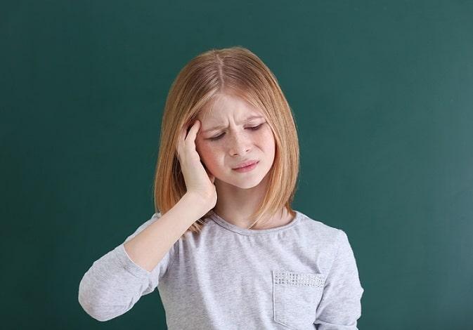 menina com otite externa aguda difusa com mão no ouvido por sentir dor