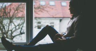 mulher com depressao sentada na janela