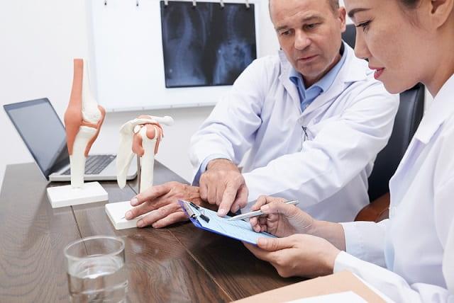 médico ortopedista discutindo história de paciente com dor crônica com enfermeira
