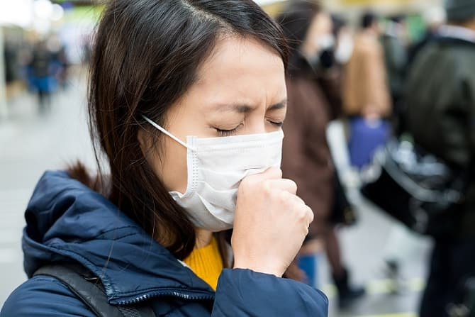 menina chinesa com máscara e tossindo devido a coronavírus