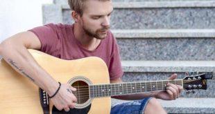 homem com depressão sentado na escada com um violão