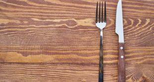 garfo e faca em cima de mesa de madeira, representando jejum intermitente