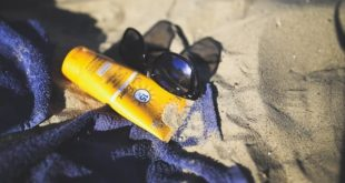 óculos e protetor solar em cima de canga, na praia, para evitar câncer de pele