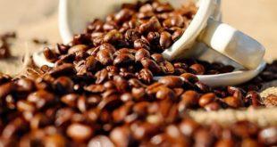 xícara jogando grãos de café na mesa