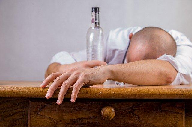 homem com intoxicação deitado na mesa segurando garrafa de vodka