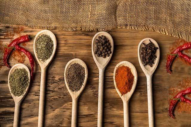 vários tipos de pimenta em colheres de pau que podem ajudar na redução da mortalidade cardiovascular